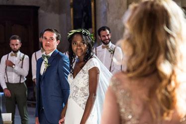 il y a un mari avec sa femme dans l'église dans le fond les témoins puis en premier plan l officiant cérémonie de mariage